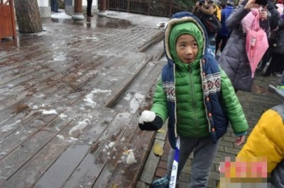 来儿童兴奋地拿着雪拍照。