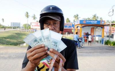 受惠的民众纷纷到银行领取250令吉现款,喜上眉梢。