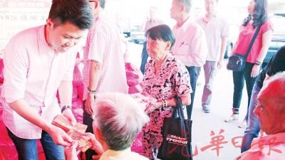 张盛闻在施赠贫老活动上,派发红包予乐龄人士。