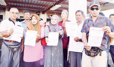 安南武吉甘榜士勿郎仄卡村民展示门牌税单据,不满市政厅向他们征收门牌税。