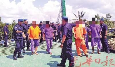几名涉嫌走私香烟的嫌犯被带上油槽船。