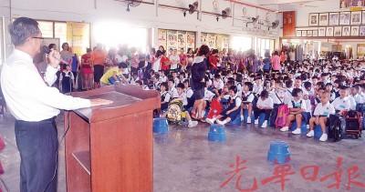 新华小学一年级新生及下午班学生在礼堂,聆听赖顺来校长的汇报。