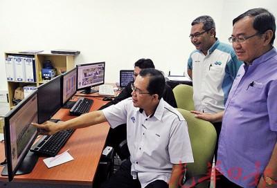 哈敏沙木里(坐者)向水利灌溉局官员了解水闸的电脑操作及监管系统。