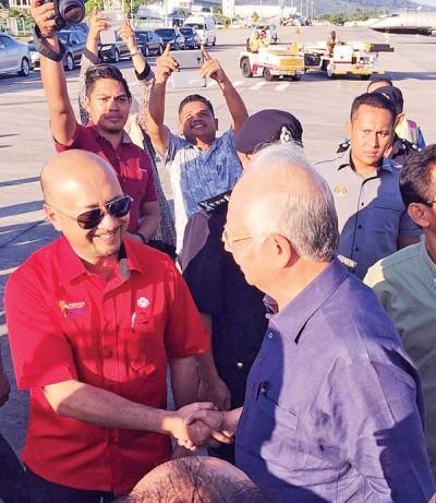 首相纳吉(右)跟前来接机的艳羡克里(左)拉手寒暄。