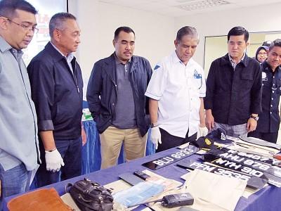 霹警方观察从匪徒车上搜出的车牌,巴冷刀及新钞等。