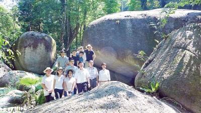 曹观友与连玉和(右2)及李文宝(右1)等在巨岩前合影。