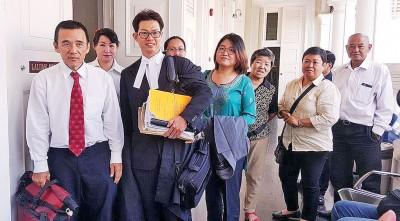 郑雨周与代表律师谢英顺以及亲友的陪同下步出法庭。