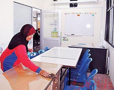 本那牙益侨学校一年级课室空荡,校工正在抹除及清理灰尘。