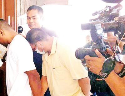被告詹源发穿着口罩避开媒体镜头。