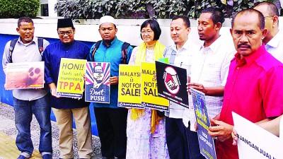 玛丽亚陈(左4起)及卡玛鲁等人,在警局外向媒体出示反泛太平洋伙伴协议的标语海报。