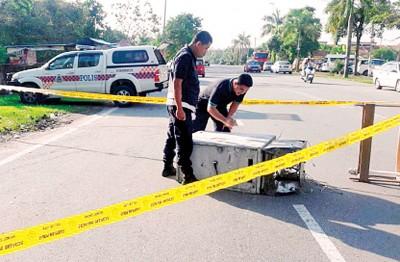 匪徒将提款机遗弃路旁,警方正提取提款机上的指纹调查。