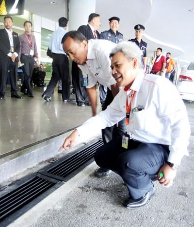 大马机场有限公司高级经理阿立夫(右)及工程管理高级经理诺士京指示槟城国际机场入境处外已加宽的排水沟。
