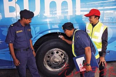 执法人员检查长巴轮胎花纹是否符合规格,左为莫革及尼沙兹万(右)。