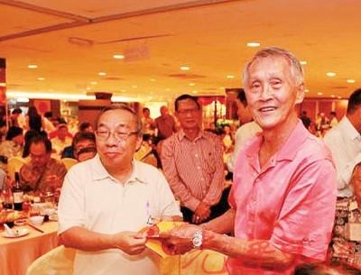 林文庆(右)在2013年出席曾执教过的1966/68年锺灵毕业生45周年纪念晚宴时,从曾任锺灵国中第12任校长的该届校友沈仁东手上接过纪念品。