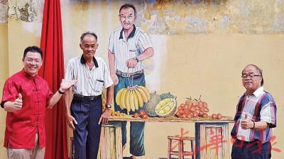 倪可敏(左)与本地画家蔡子文(右)及壁画上的人物何财在壁画前合影。