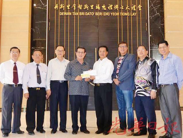 方天兴(左5)从陈锦龙(左4))手中接过支票,见证者有王羾信、萧楚钗、林家仪、洪来喜、陈耀星及叶国文。