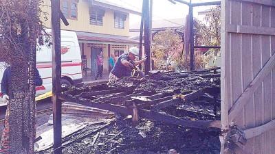消拯人员在被烧毁的木屋展开调查工作。