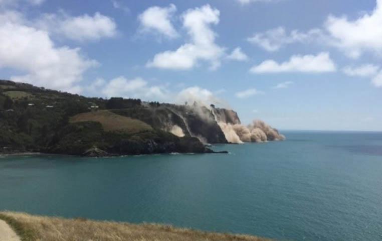 沿岸一处悬崖冒起烟尘。