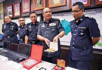 莎菲宜(右二)由建功警官及警员陪同,在记者会上展示警方起获的赃物。
