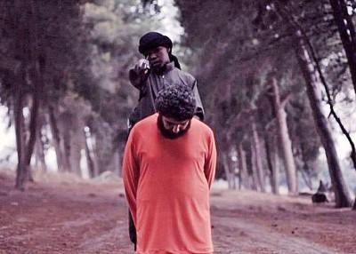 男童把身穿橙色囚衣的俘虏押到森林再斩首。