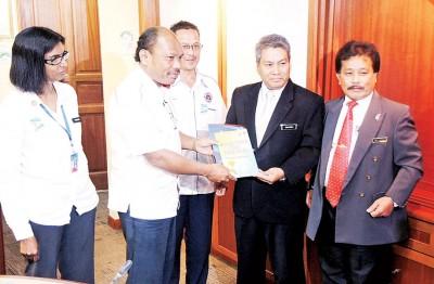 全国反毒机构行动组副总监依沙阿武达力(左2)赠送纪念品予槟州政府副秘书嘉沙里,左1为槟州反毒机构主任姆宁玛。