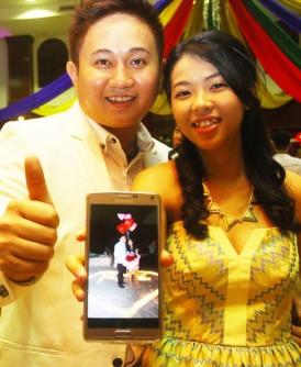 尤勇胜(左)及陈嘉璧出示两人在峇都丁宜沙滩星巴克求婚的照片。