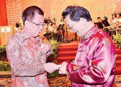 《光日报》董事骆南辉(左)同黄惠康相见欢,连互相交换名片。