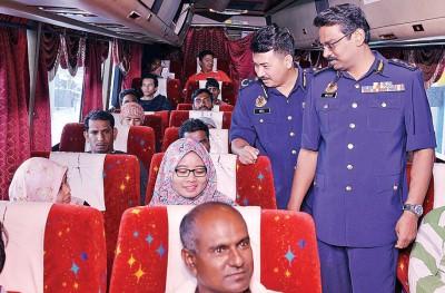 瓦鲁(右)巡查巴士时向回乡的乘客问好。