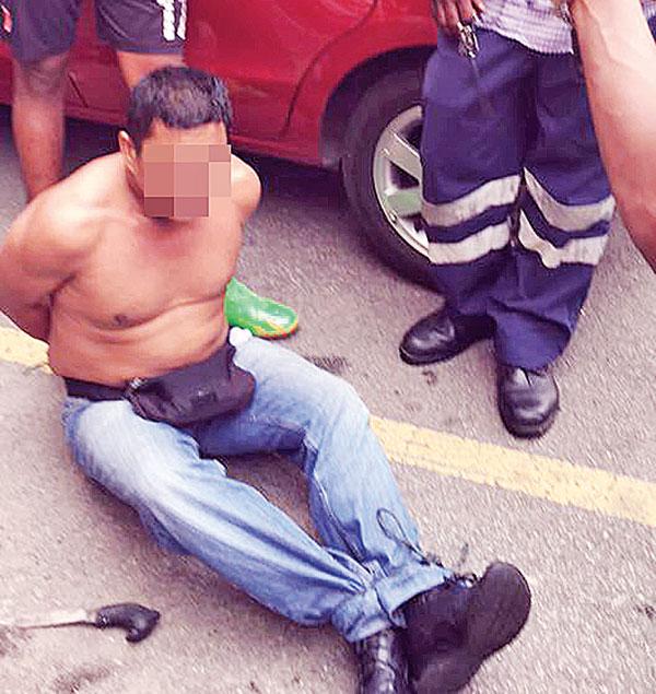匪徒手脚被绑,被公众看守以防他逃脱。(脸书照片)
