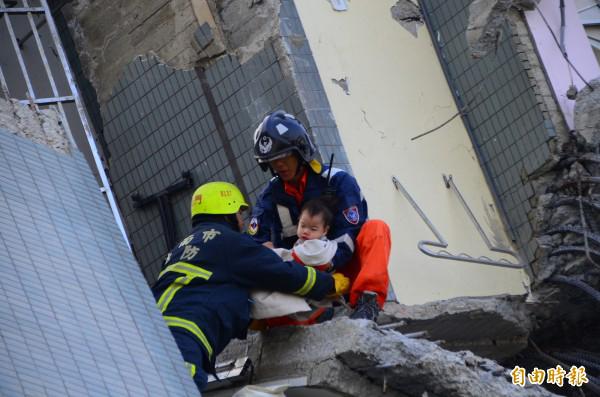 搜救人员从倒塌大楼内救出婴孩。