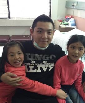 台南地震生还者黄洸伟(中)与两名小妹妹林菲(右)、婷惟(左)在获救后首次见面,并紧紧相拥。(中央社照片)