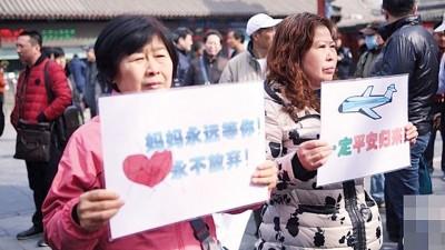 家属在雍和宫举起纸牌,祈望失踪亲人平安归来。