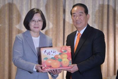 2人结束闭门会议后,宋楚瑜(右)赠送代表亲民党颜色的橘子给蔡英文(左),也取其谐音再创新局。(中央社照片)