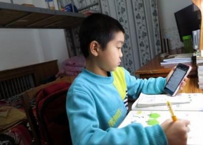 小三学生李归斌正在微信查看老师派发数学题。