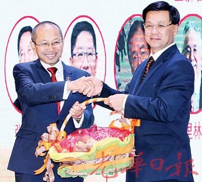 方天兴(右)赠送水果礼篮予大会开幕人阿都华希。