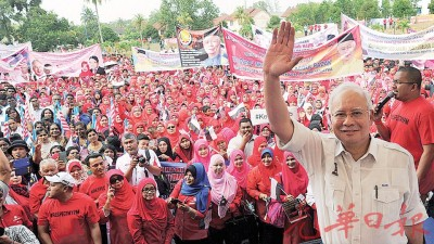 """纳吉周六上午与在关丹做的""""首相团结集会"""",于诸多支持者前为镜头挥手示意。"""
