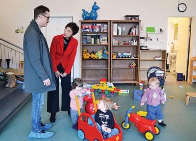 新加坡总理公署高级政务部长杨莉明(左2)在丹麦参访当地托婴设施时,与一名家长交流。