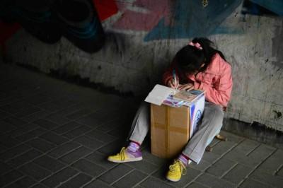 晓琪将纸箱当作课桌,独自专注地温习功课。