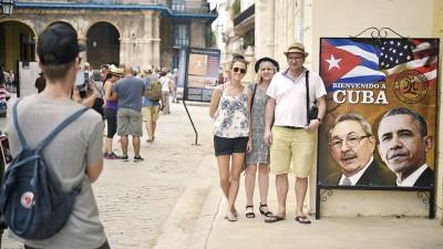 古巴首都一家餐馆挂出画有卡斯特罗与欧巴马头像的巨大彩色宣传画,吸引游客拍照留念。(法新社照片)
