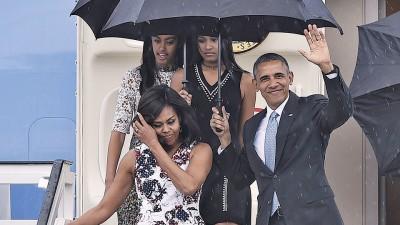 欧巴马和妻子步出机舱,望在座人士挥手,紧跟着的还有两名女性儿马利亚同萨沙。(法新社照片)