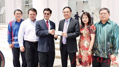 张润安(右3)移交100万令吉支票予方天兴。左起为钟来福、张凯翔、刘碧珍与陈耀星。