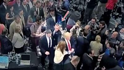 当时菲尔茨(浅色衣者)上前追访特朗普(红色领带者),疑被莱万多夫斯基(箭头指处)拉开。