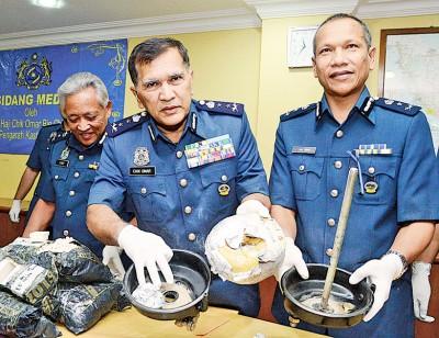 仄奥玛(中)和肃毒组官员展示从汽车零件内起获的冰毒。