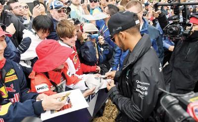 汉密尔顿(右)每当先后三次练习开始前,以及粉丝互动签名。