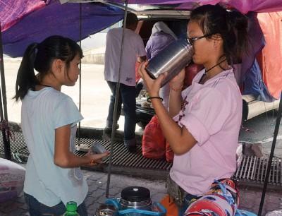 炎热的天气,街边小贩及女儿也得多喝水。