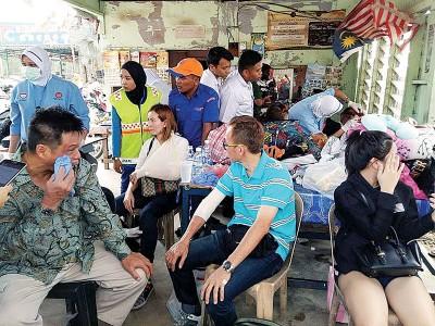 部分受轻伤的巴士乘客,接受救护人员的治疗。