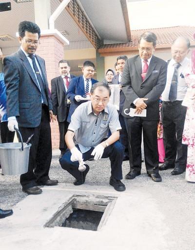 马汉顺亲自把消灭孑孓药粉放入学校的沟渠。