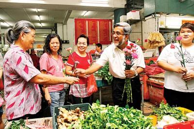 阿都玛力议员派送500朵康乃馨,瞧买菜的安娣们多开心。
