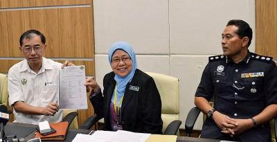 马汉顺(左)向媒体展示化验报告,在场者为朱丽达(中)及纳西尔警监。