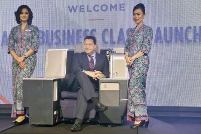 """保罗安德鲁(中)""""兼任""""模特儿,为A330-300商务舱主持推介仪式。"""